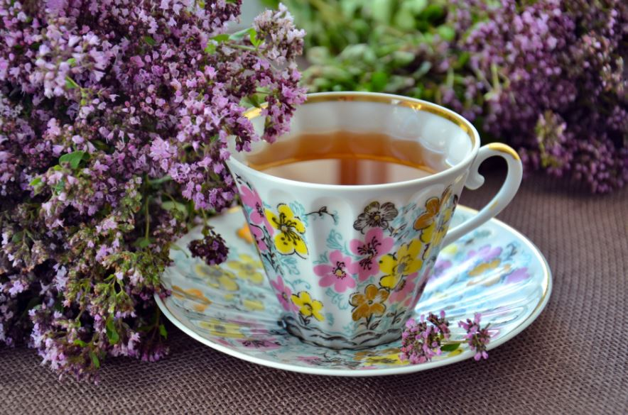 a colorful ceramic cup with tea in it, surrounded by lavender flowers
